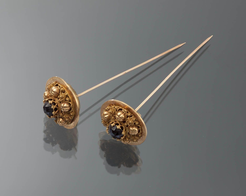 Paar 18 karaat gouden kapspelden, ingelegd met granaat. Deze mutsenspelden zijn gedragen door een vrouw op Noord-Beveland, omstreeks 1870. De spelden werden horizontaal achterwaarts in de sluiermuts gestoken, tussen de krullen van het oorijzer.  #NoordBeveland #Zeeland