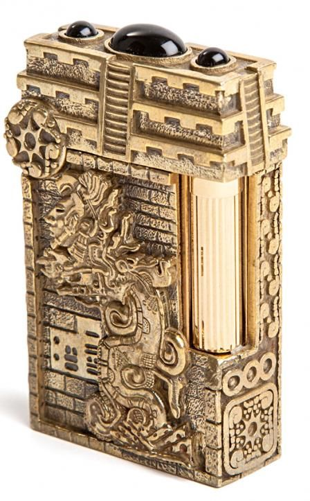 APOCALYPSE TOURNAIRE LINE 2 LIGHTER:  Fashioned from bronze, each pen & base take shape in the hands of the artist. It is chased, engraved, polished and finishes with a gold colored patina. On the top, 3 Obsidian Cabochon in the spirit of Mayan's Temple. #Apocalypse #STDupont