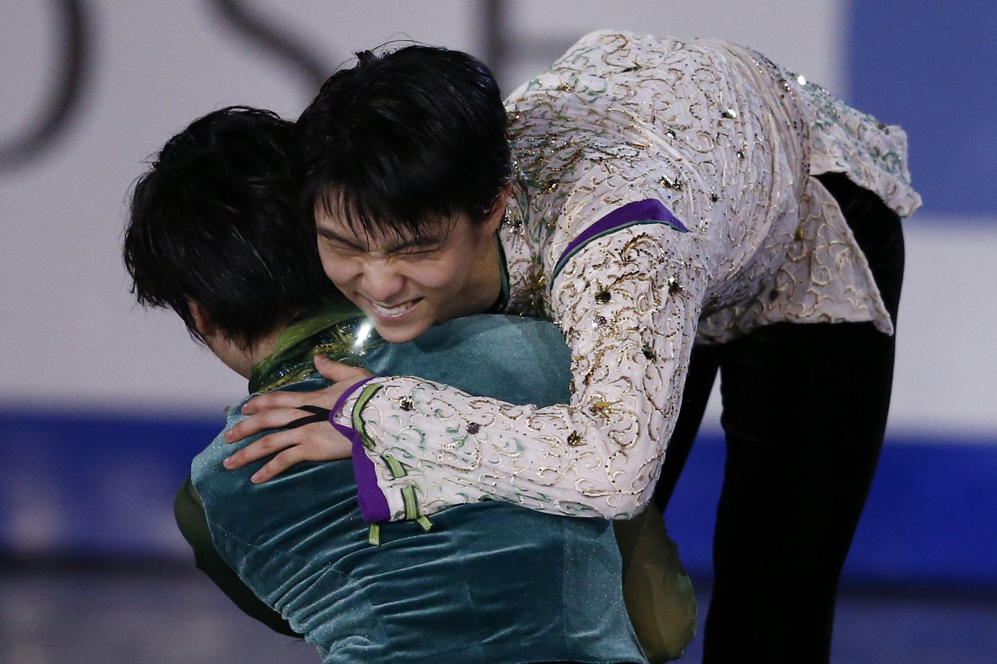 Gold medal winner Yuzuru Hanyu of Japan, right hugs Shoma Uno of Japan who won the bronze in the Men's final of the Grand Prix Final figure skating competition in Barcelona, Spain, Saturday, Dec. 12, 2015. (AP Photo/Manu Fernandez)