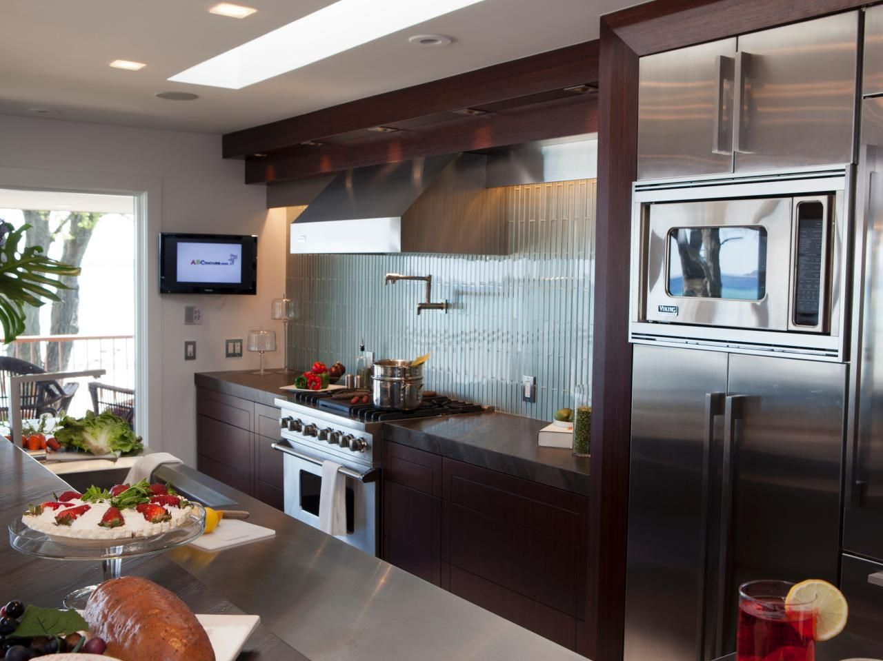 The dark-stained wood cabinets are a nice contrast to the stainless ...