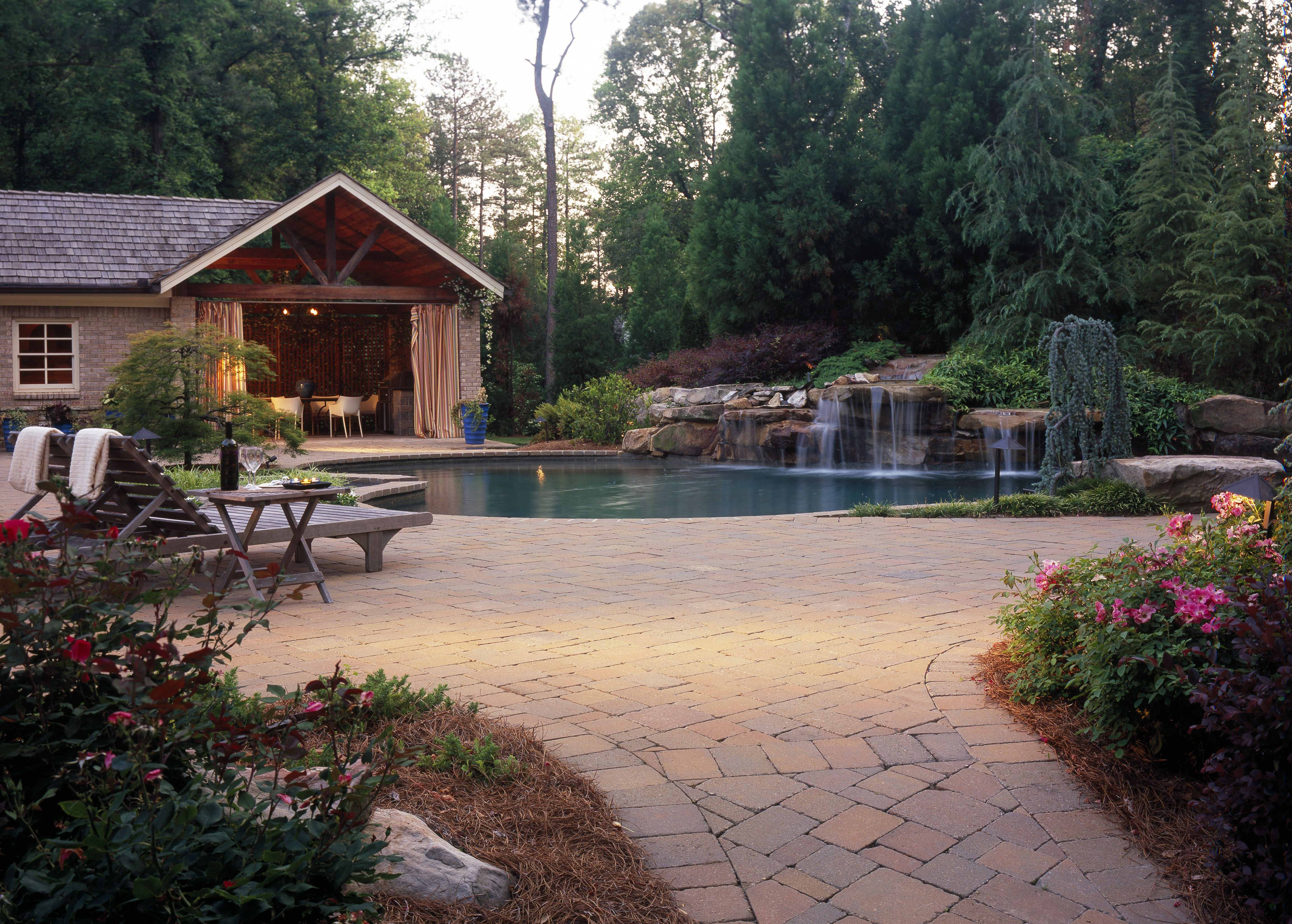 red paver pool deck with natural stone waterfall. outdoor living