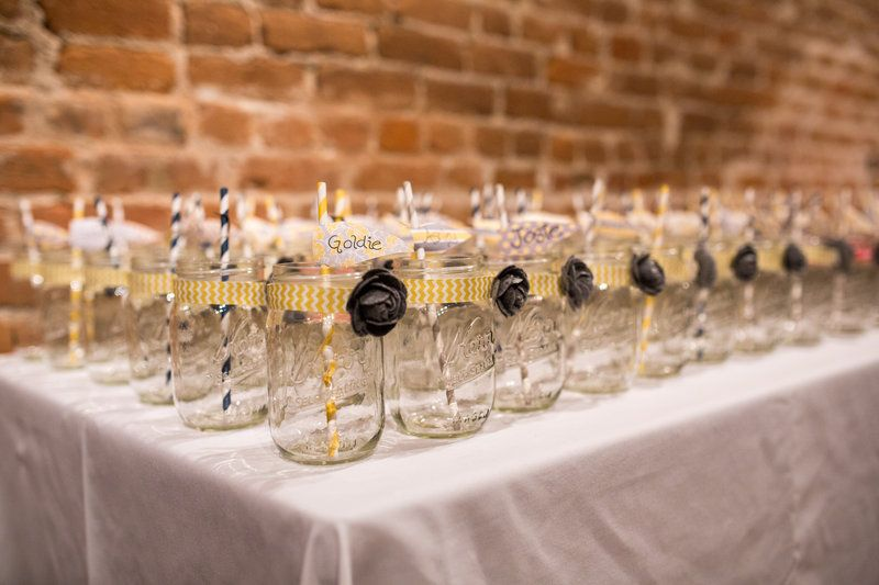 Our wedding favors were mason jars that we decorated by hand flowers for girls and bow ties for boys They also served as out escort cards each flag had the guest name and the table number on the back Photo By robert godridge photography