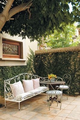 A Courtyard Featuring Stylish Wrought Iron Furniture Enhances The