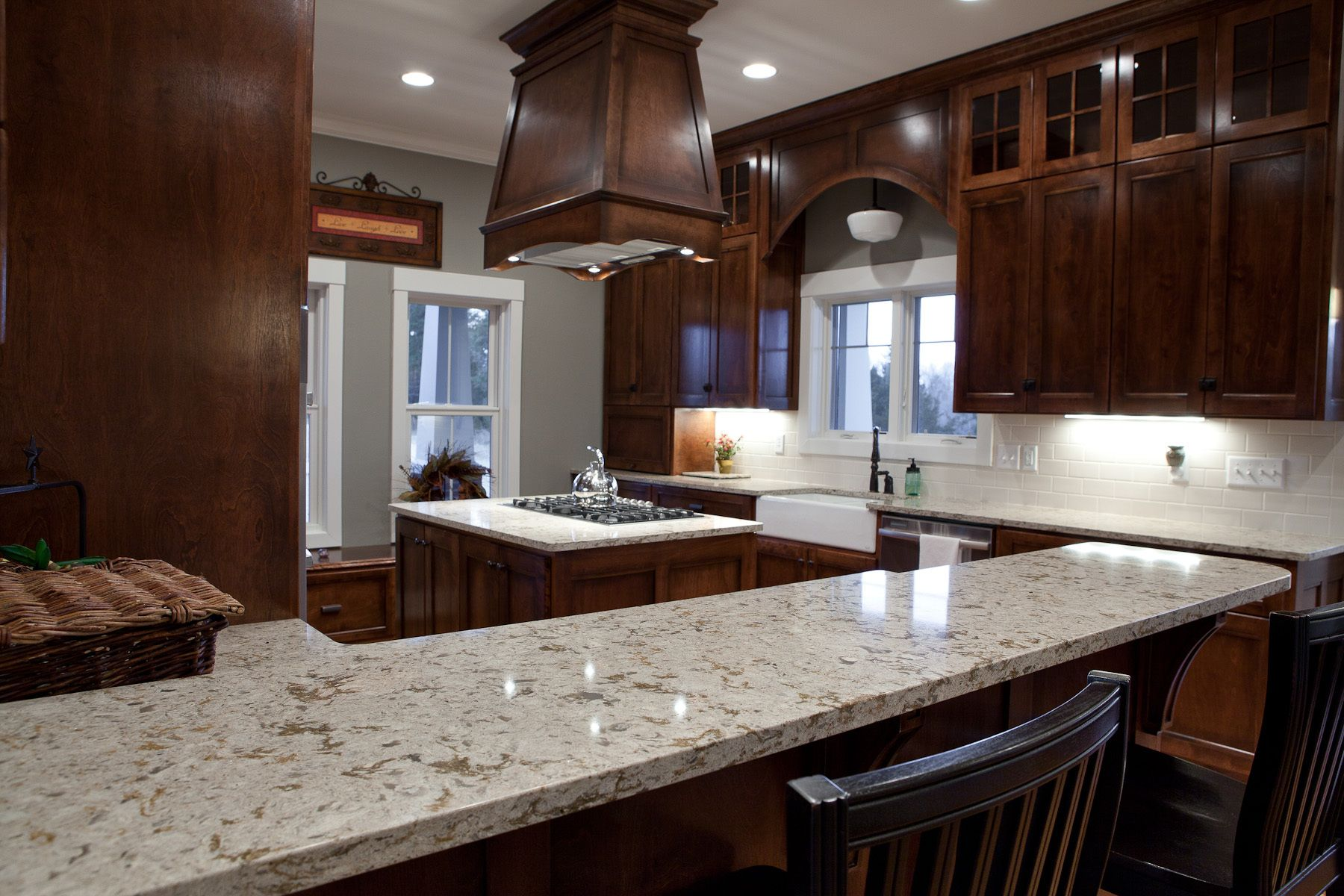 Fantastic wooden range hood over island with black stove What is the whitest quartz countertop