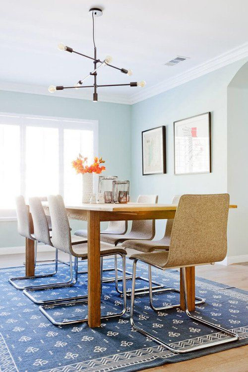 Pastel blue dining room with fun patterned rug and cool designed chairs