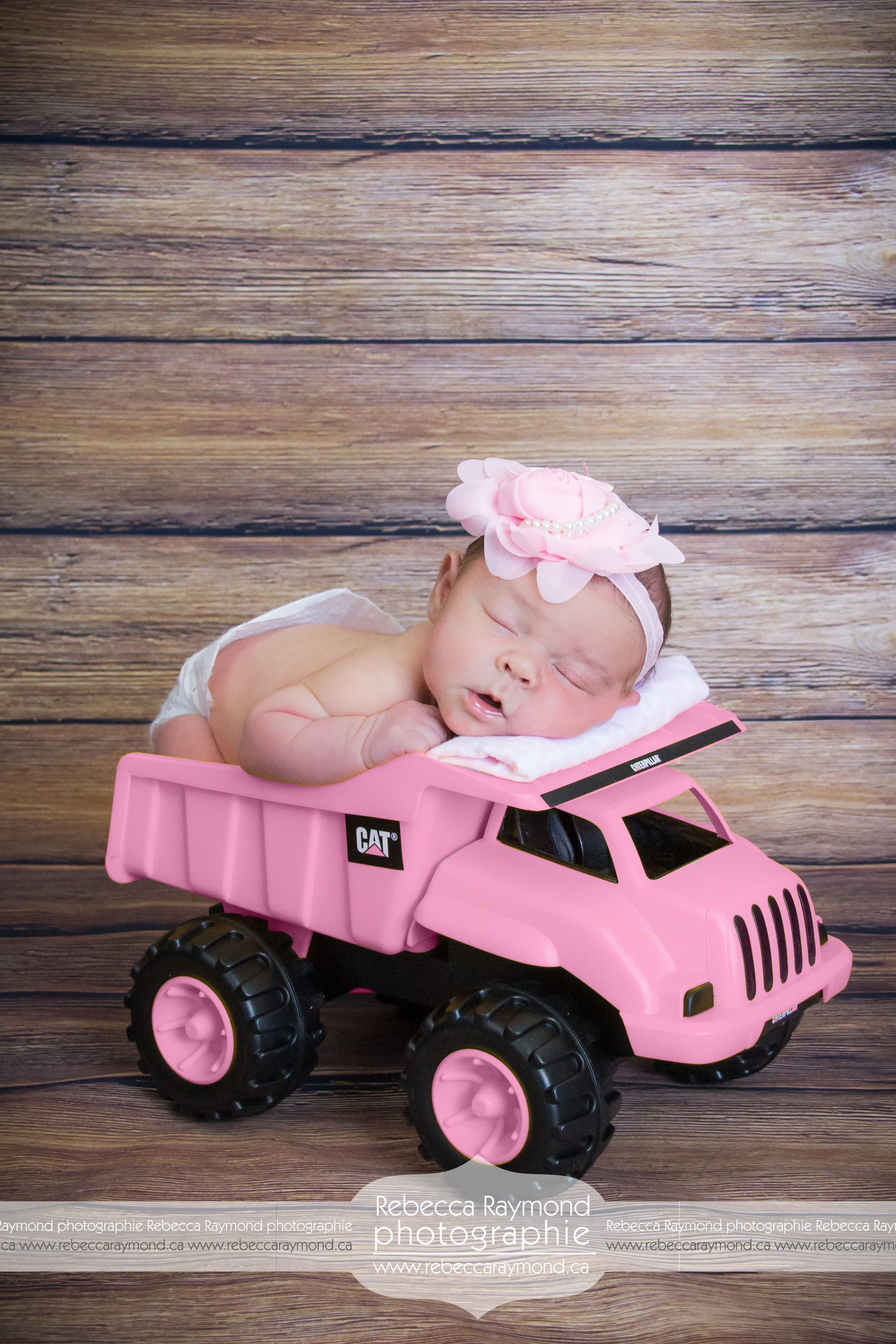 Newborn in a pink Tonka Baby sleeping toys photoshoot newborn ideas pose and positions