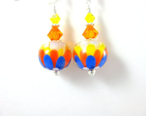 Handmade encased Summer flower earrings featuring royal blue, orange, yellow and white SRA artisan crafted lampwork beads; sterling silver; and Sun and Citrine AB Swarovski crystals.  These beautiful earrings are composed of beautiful 14mm lampwork beads created by an SRA lampwork artist. The beads have royal blue, orange, yellow and white petals encased within crystal clear glass. Sun and Citrine AB Swarovski crystals compliment the beads and add sparkle. Sterling silver beads, head pins…