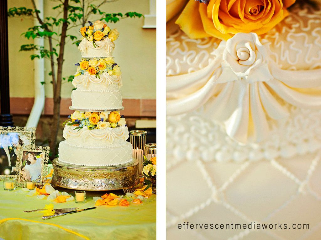 three tiered wedding cake with yellow and blue roses. Draped ...