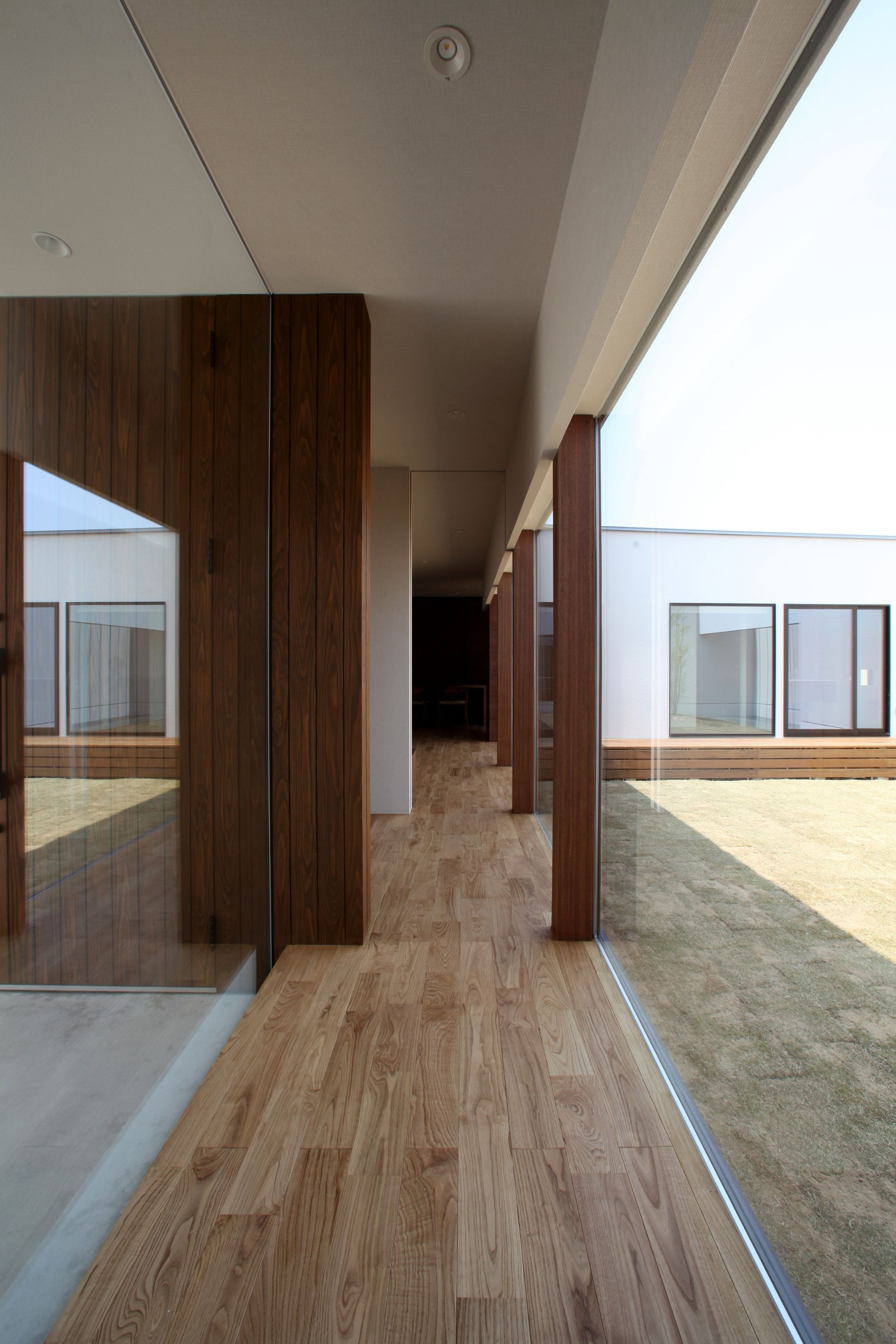 廊下の両側をガラスにすることで 中にいながらも外に出たような開放的