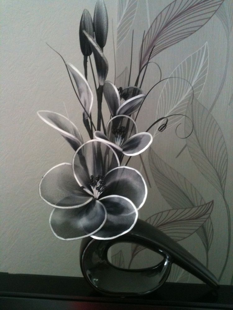 Artificial flower arrangement in black white nylon flowers in shaped vase