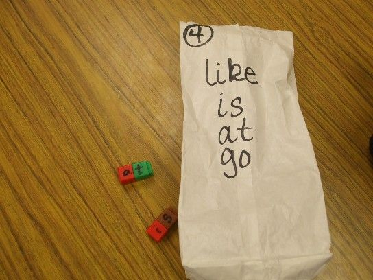 Children reach into a bag and pull out unifix cubes with letters written on them. They then make the sight words listed on the outside of the bag.