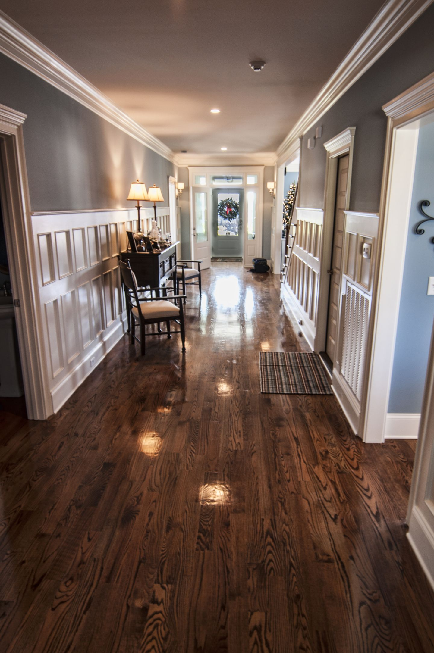 Entryway with dark wood floors, blue walls, and white trim