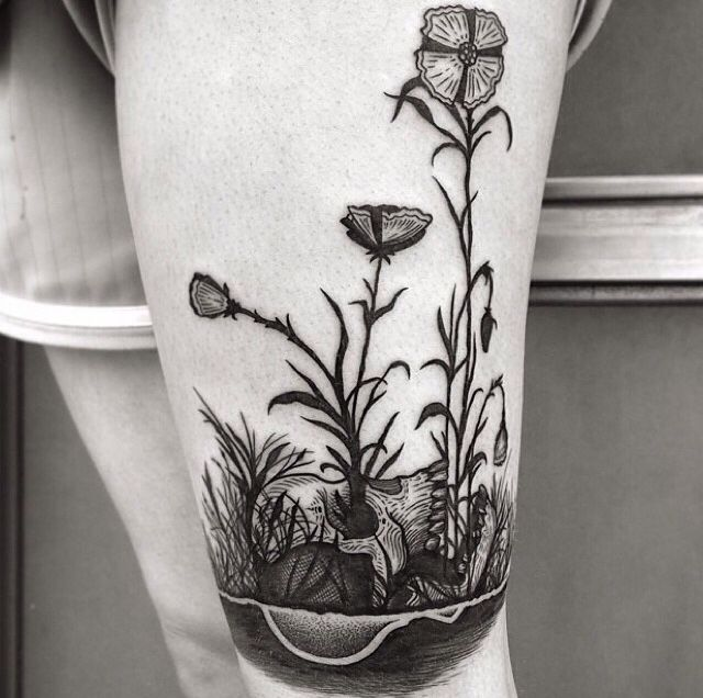 Flowers growing out of a skull tattoo