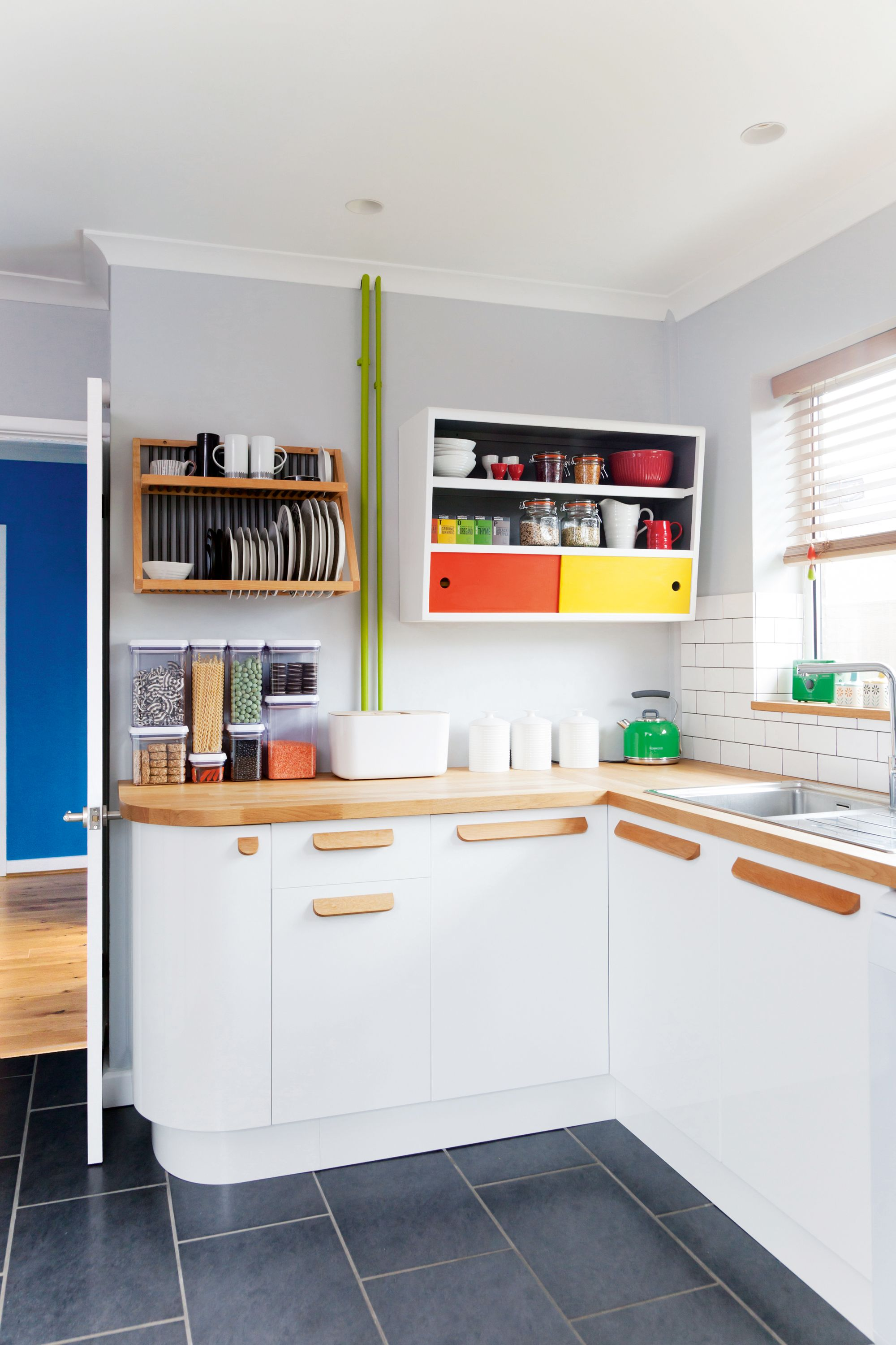 White Kitchen With Updated Wooden Handles And Brightly Coloured