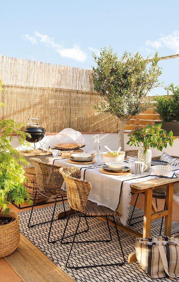Comedor en la terraza junto a la barbacoa rodeado de plantas ...