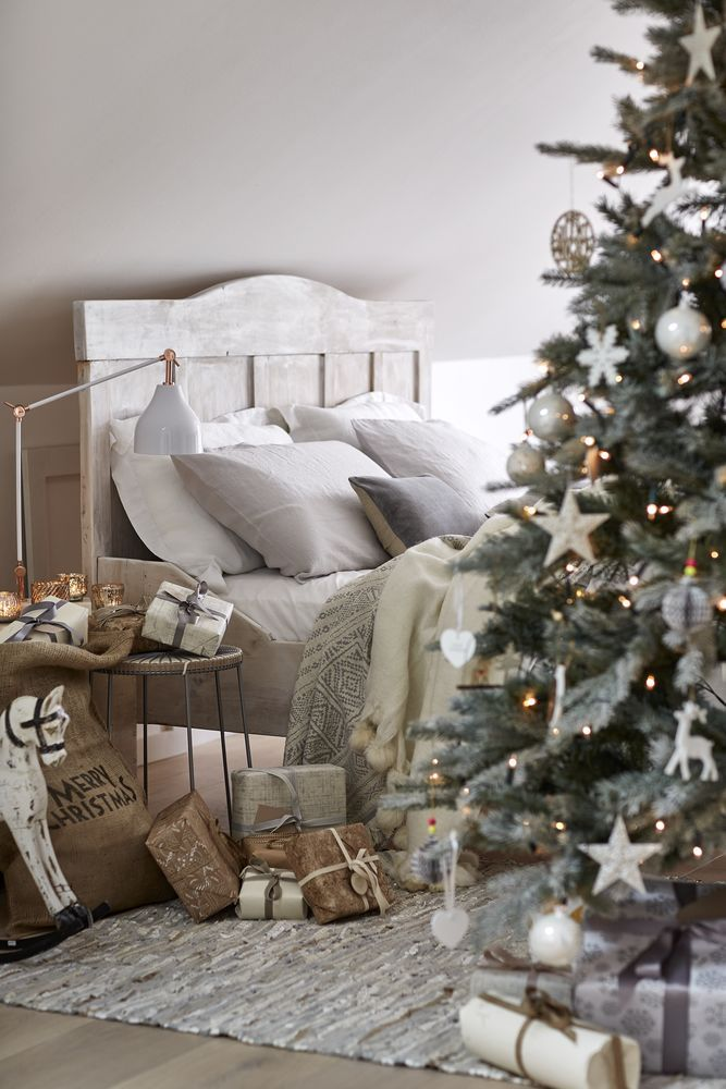 Christmas bedroom: Layer natural bedlinen with throws in soft hues on a rustic wooden bed frame. Introduce contrast with a white table lamp and touches of copper. For more bedroom ideas visit housebeautiful.co.uk