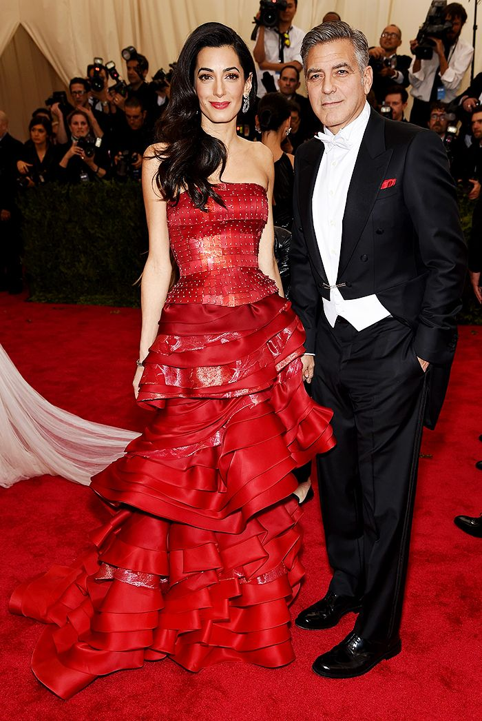 Amal Clooney stunned in a intricate and voluminous John Galliano for Maison Margiela gown in red with George Clooney at the 2015 Met Gala