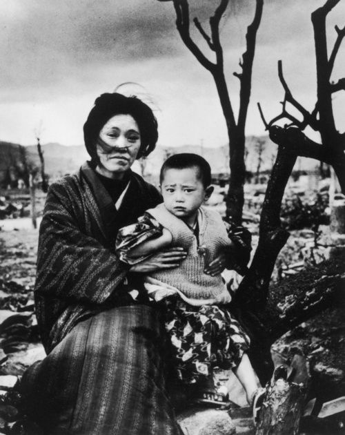 Likes | Tumblr/ A mother and child sit amongst the ruins of Hiroshima for months after the atomic bomb, 1945.
