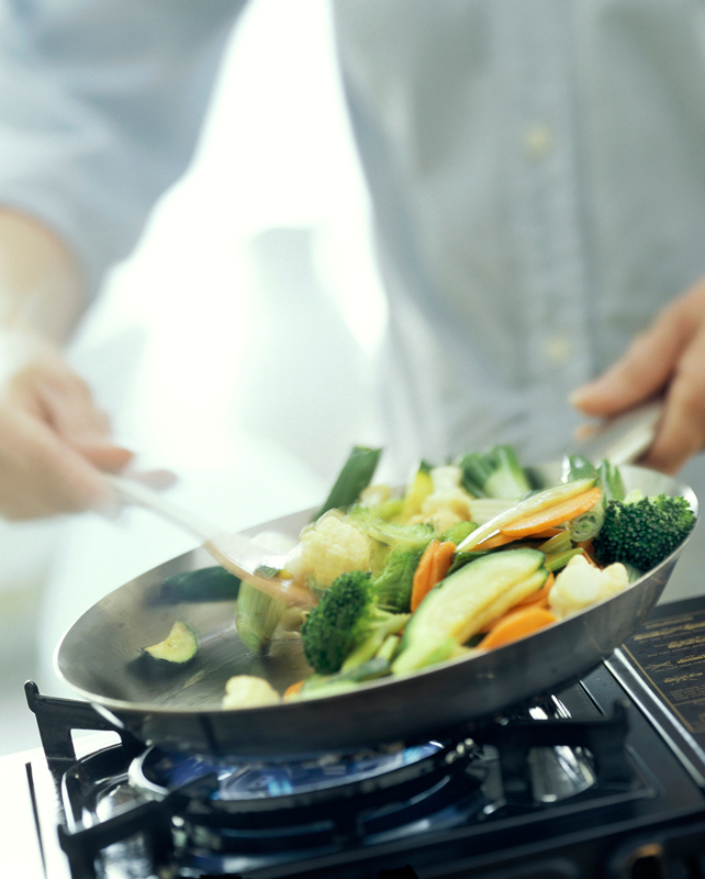 Vegetable stir-fry cooking on a gas stove