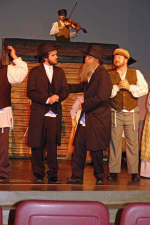Mendel Is Wearing A Traditional Long Black Coat Black Trousers Black Vest White Shirt Prayer Shawl And Fiddler On The Roof Costume Rentals Theatre Costumes