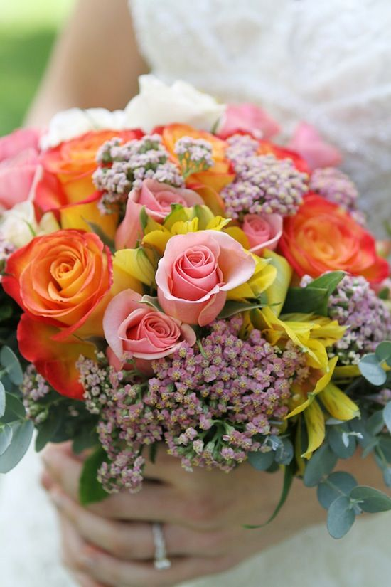 Bridal bouquet in pinks, corals, yellows, and peaches.