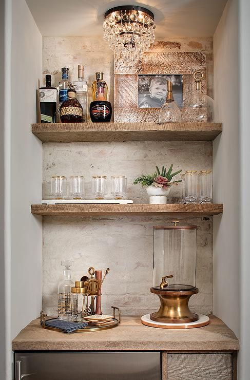 Illuminated By A Gorgeous Crystal Flush Mount Styled Rustic Floating Shelves Are Fixed Against A White Bric Small Bars For Home Home Bar Designs Bars For Home