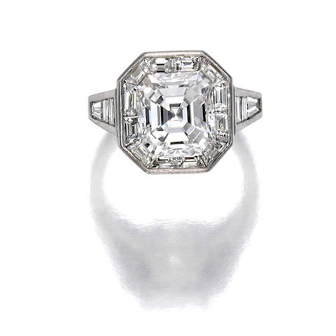 A diamond ring centering a 5.13 carat cut-cornered rectangular step-cut diamond, with a baguette-cut diamond surround and shoulders; remaining diamond weight 2.60 carats; mounted in platinum.