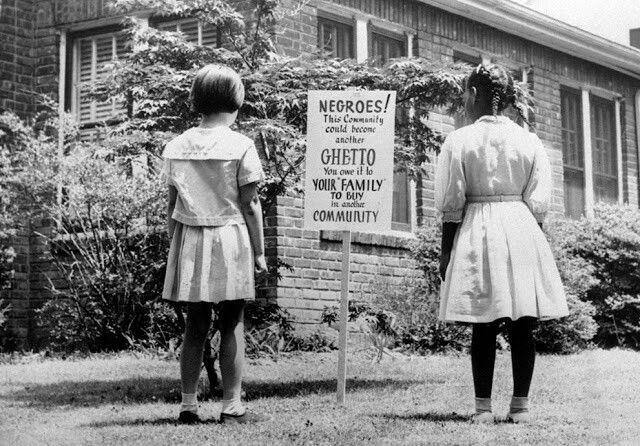 "An African American and a white girl study a sign in the integrated Long Island community of Lakeview, New York, on April 1962. It reads ""Negroes! This community could become another ghetto. You owe it to your 'family' to buy in another community."" The sign was an attempt to keep African Americans from exceeding the number of whites who want to live in an integrated town. (AP Photo)"