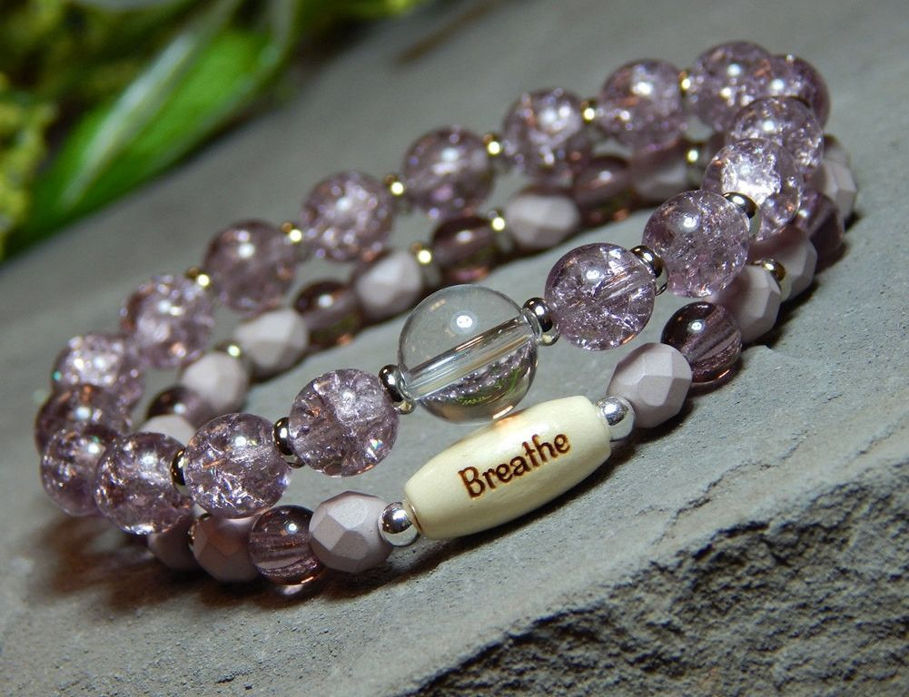 "Inspiring set of 2 purple bracelets are made with a 10mm Crystal Quartz focal bead, a natural wood bead engraved with ""Breathe"" surrounded by high quality czech beads in 8mm and 6mm. Crystal Quartz Pr"