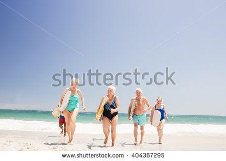 Senior friends holding surfboard on the beach - stock photo