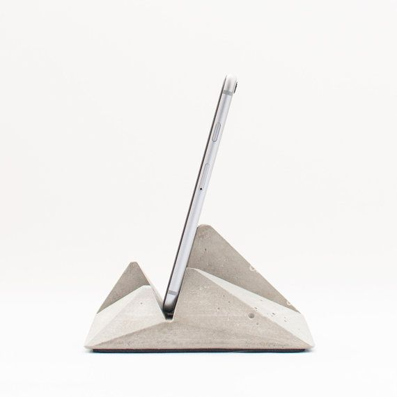 Modern smartphone and tablet stand made in concrete to hold your cell phone or tablet on your desk, your bedside table, at your kitchen, at your workspace or anywhere you may need it. It´s unique in its kind because thanks to its carefully designed geometry, it can be used in different positions to hold various sized devices . It´s made in grey concrete with a geometric pyramidal design inspired on origami paper toys. An elegant iconic and modern sculptural object hold and highlight your…