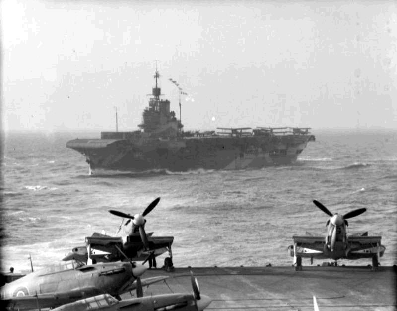Great Britain's HMS Indomitable fleet aircraft carrier astern HMS