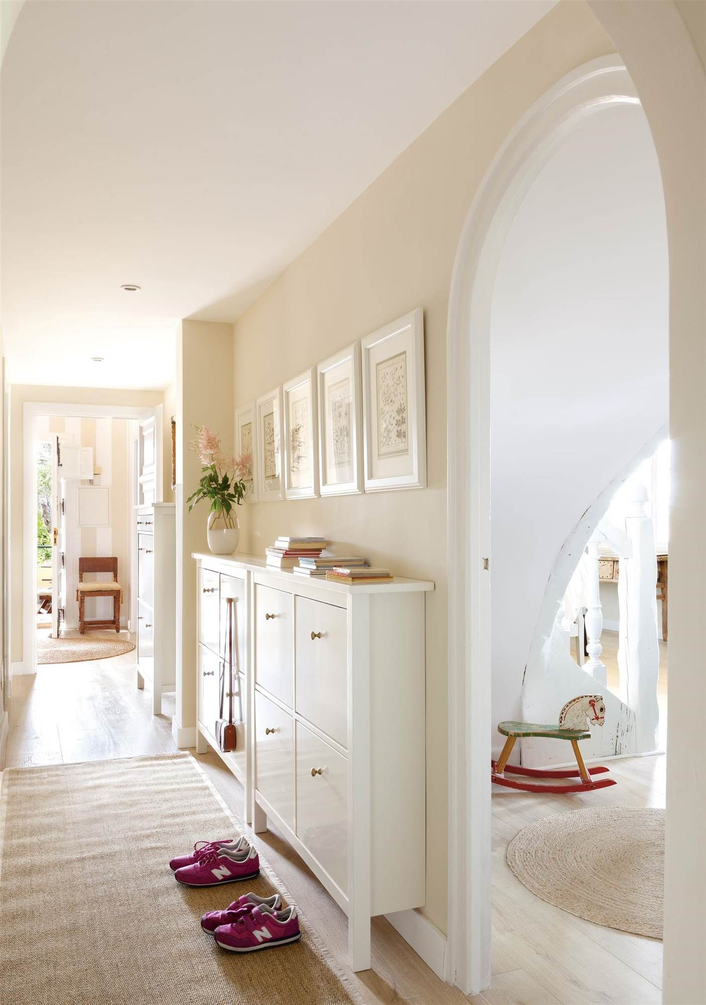 Pasillo con muebles zapateros alfombra y cuadros for Entraditas con zapatero
