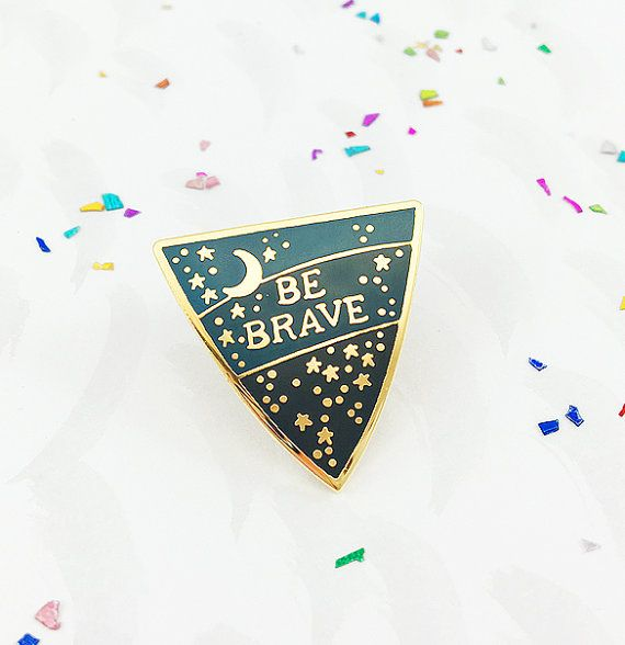 **Free UK Shipping on all pin badges in the Bonbi shop!** A sweet protective shield shaped pin with a positive reminder set out among the stars! The pin badge with it's hues of enamelled night sky blues is an original design by Bonbi Forest's Lee May Foster-Wilson and features the phrase 'Be Brave' surrounded by shining metallic stars and a crescent moon. Designed to be like a modern talisman with it's message of positivity, ambition and looking forward it is the perfect gift for someone ...