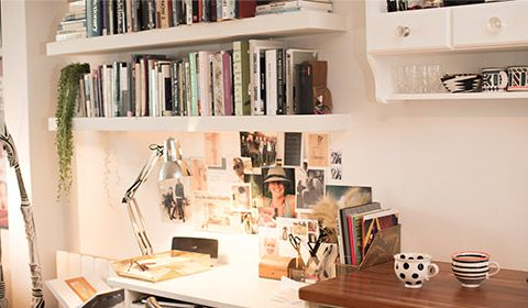 A silver desk lamp shines over a white gloss desk, whilst photos, cuttings and poloroids are arranged on a wall. Two shelves sit above the desk stacked with books
