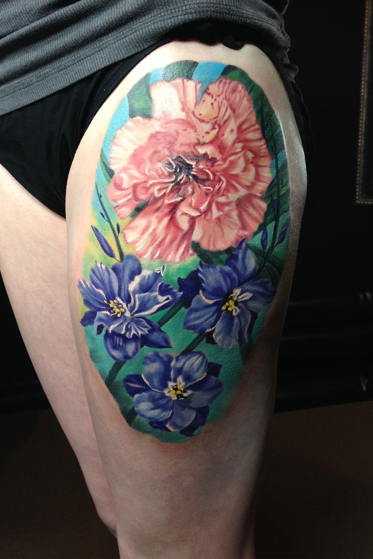 Carnation and larkspur flower color thigh tattoo by Monte Livingston at Livin