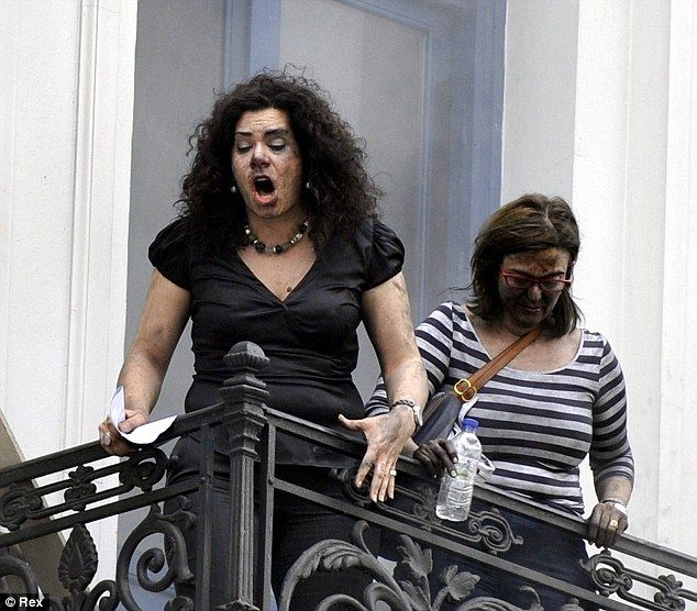 Athens: two employees, covered in black from the smoke, cry out in terror from the top floor of the Marfin Egnatia Bank where they were trapped.