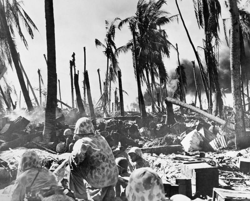 American Marines approach a group of Japanese-occupied buildings, reduced to rubble during the Battle of Tarawa, a Pacific atoll in the Gilbert Islands (now Kiribati), in November 1943. In the background, smoke is rising from an oil-dump hit during the shelling.