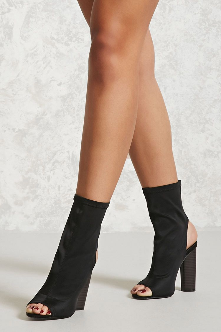 79c7778c19d A pair of sock boots featuring an open toe, a cutout back, and a stacked  block heel.