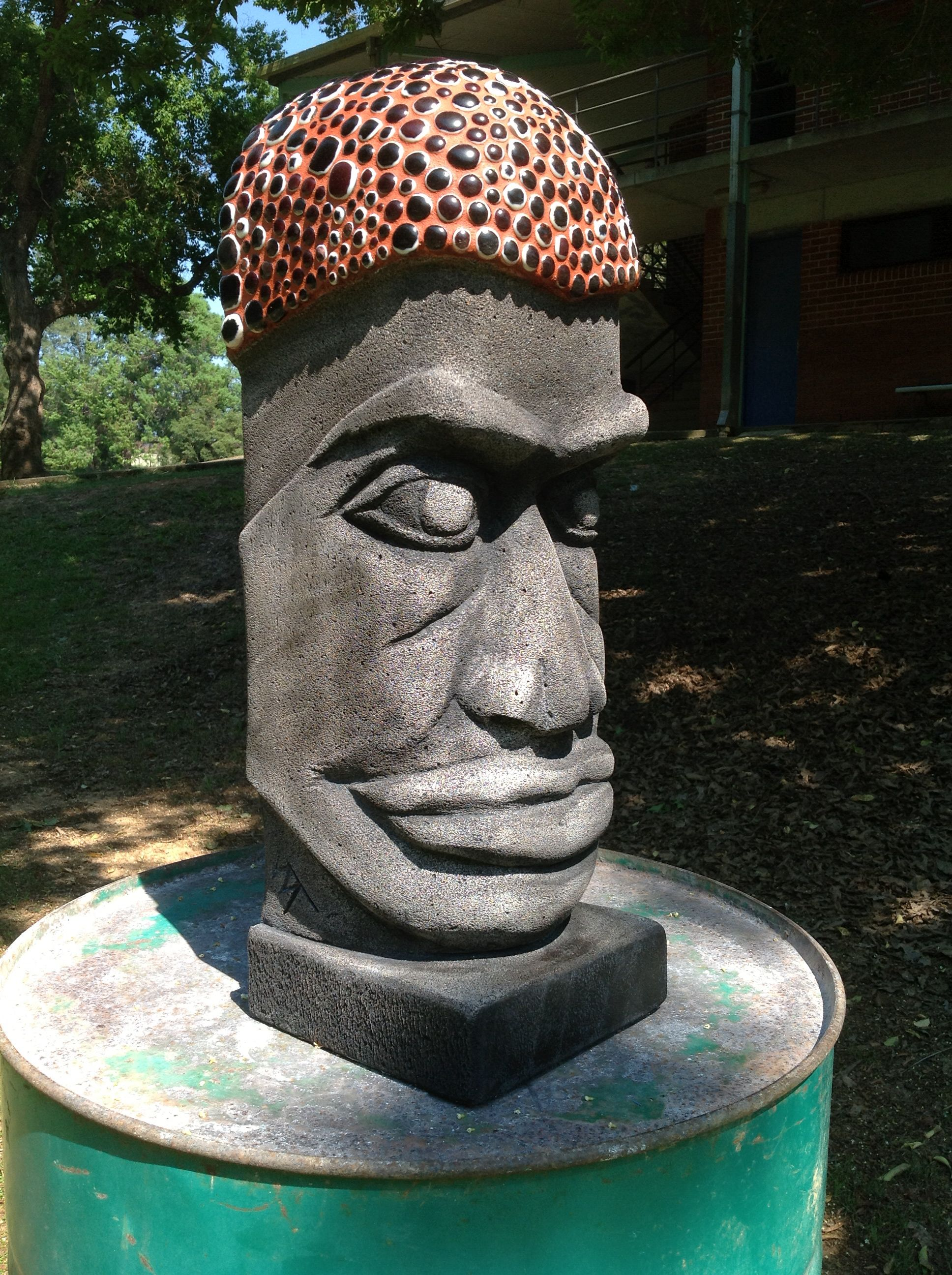 Carved stone head with mosaiced hat/hair ?