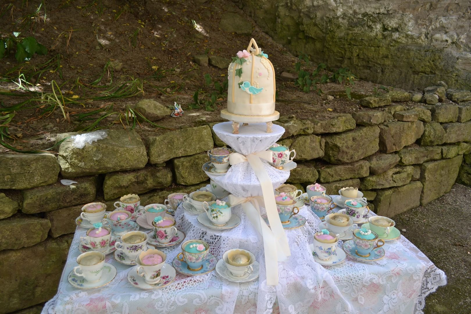Tea party dessert spread with a lovely cake and cupcakes in tea cups and saucers Boutique Baker