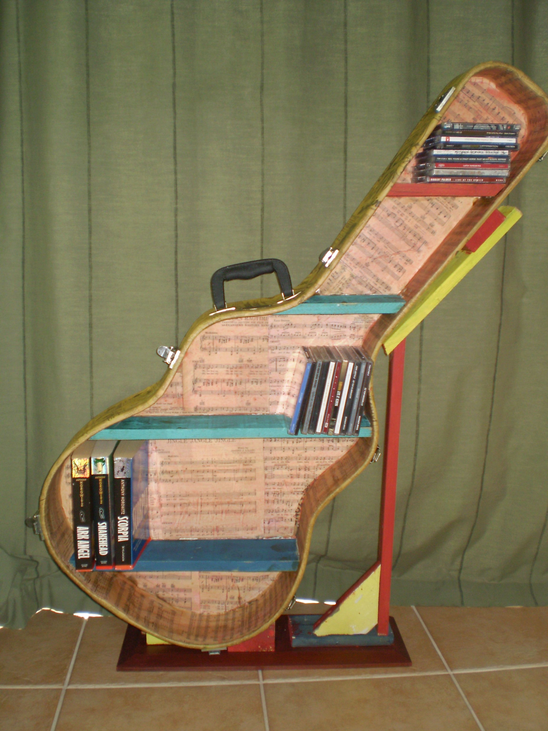 a guitar case re purposed into a cd book shelf decoupage old news