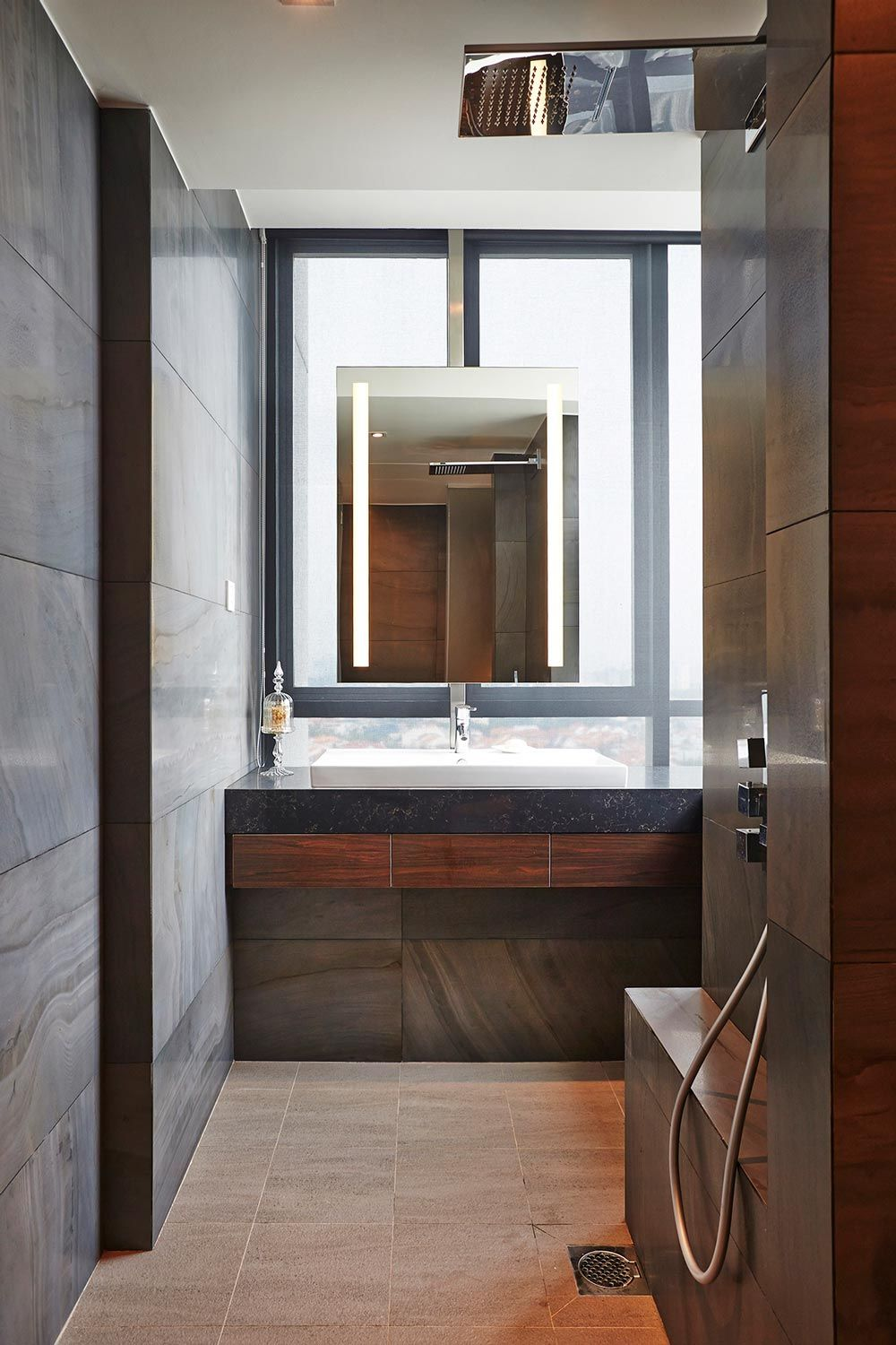 A Resort Style Bathroom With Wood Laminates And Stone Like Tiles Interior Design Toilet Bathroom Styling Lighted Bathroom Mirror