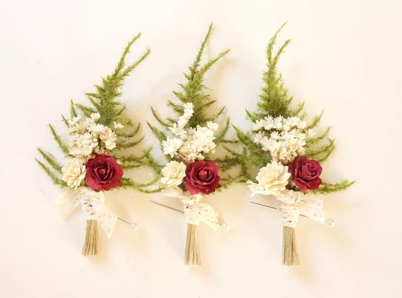 B O U T O N N I E R E / B U R G U N D Y R O S E This woodland style boutonniere is perfect for a rustic, woodland ceremony. This pin features feathery faux asparagus ferns, dried star flowers and paper tea roses in burgundy marsala. It is just perfect for the groom that