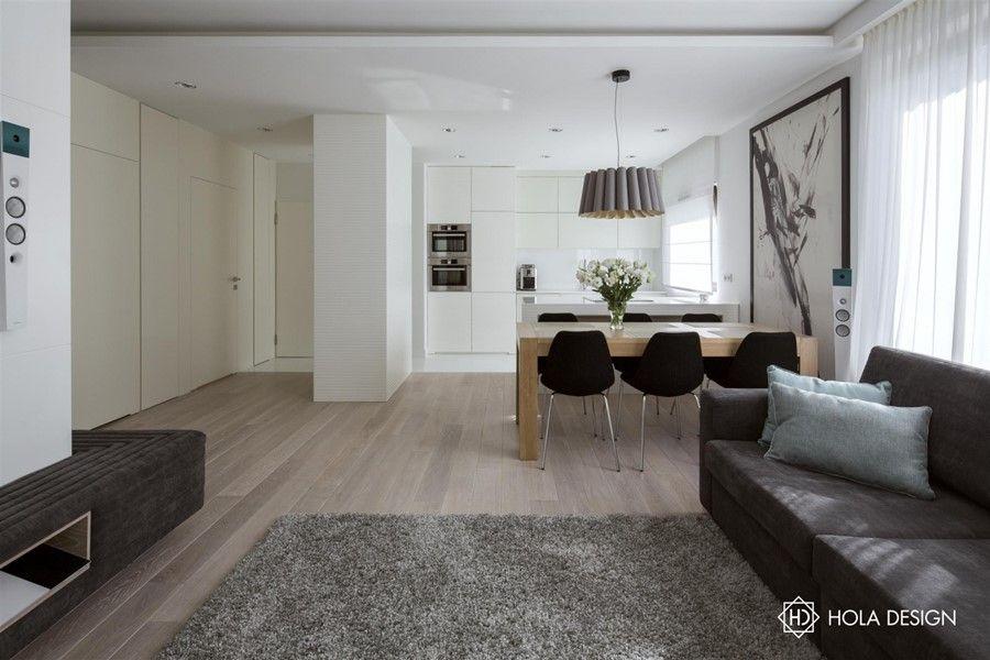 Aranżacja małego mieszkania w stylu nowoczesnym została oparta o złamane odcienie koloru białego. Powstała uporządkowana przestrzeń pełna światła.