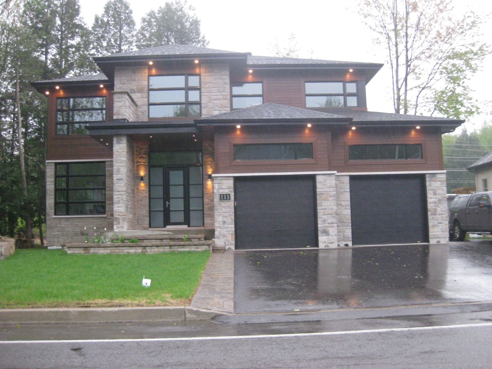 Maison moderne avec portes de garages noires. Fenêtres ...