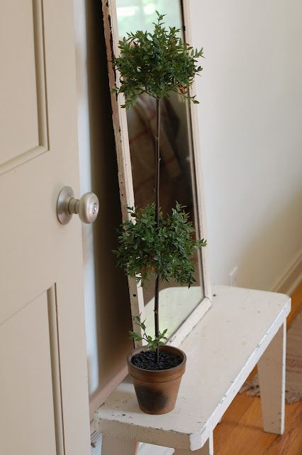 An antique full-lenth mirror and topiary sit on a chippy white bench right inside the door.