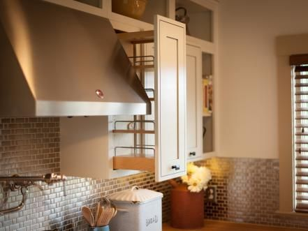 Storage options galore include wall spice pullouts. A pot filler and stainless steel hood, though utilitarian, lend visual interest.