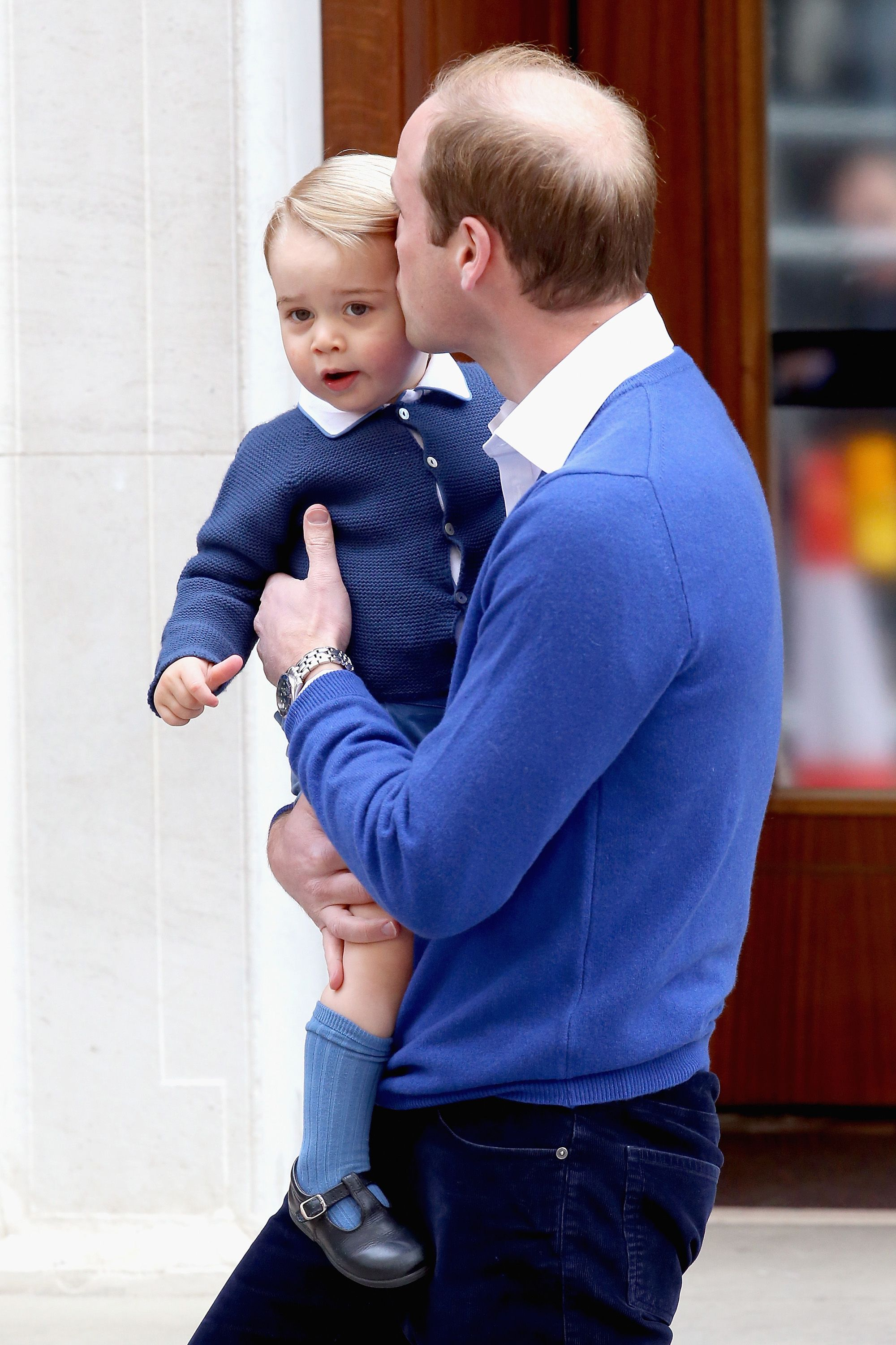 Prince William plants a kiss on his son before taking him to meet his new sister.   - HarpersBAZAAR.com