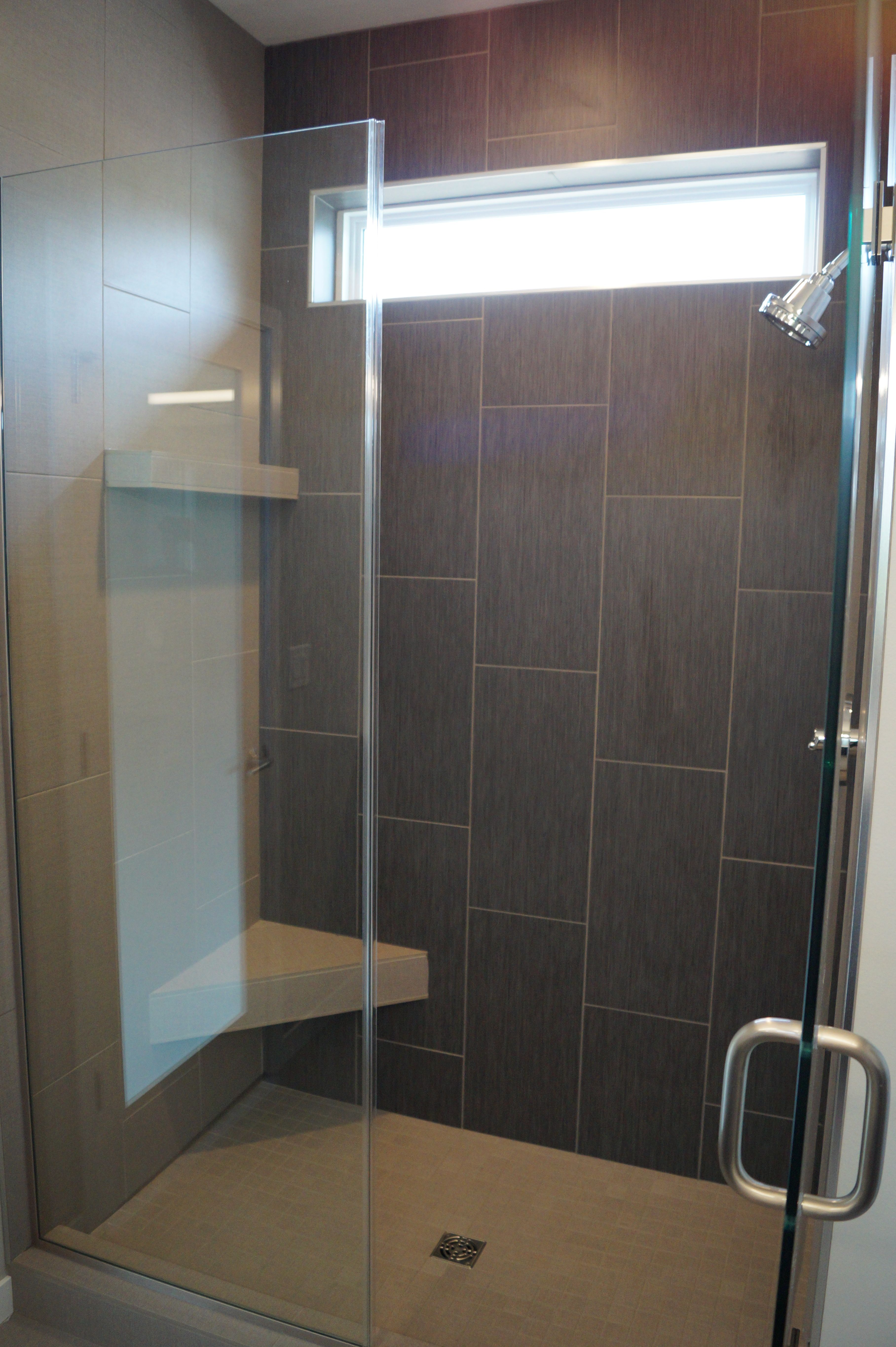 Custom tiled master bath shower. With a dark gray striated back ...